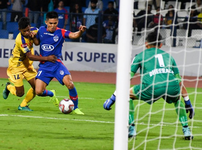 PACY: Sunil Chhetri (left) of Bengaluru FC attempts to get past a Kerala Blaster defender during their ISL game at the Sree Kanteerava stadium in Bengaluru on Wednesday. DH PHOTO/BH SHIVAKUMAR