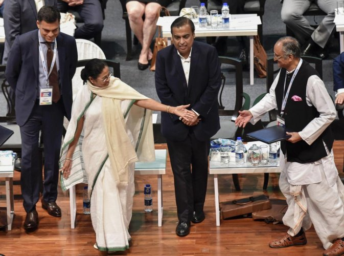 West Bengal Chief Minister Mamata Banerjee gestures at State Finance Minister Amit Mitra as Reliance Industries Chairman Mukesh Ambani and JSW Group Chairman Sajjan Jindal (L) look on, during 'Bengal Global Business Summit 2019' in Kolkata on Thursday. PT