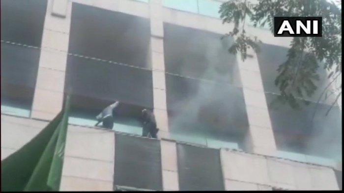 Thick smoke could be seen billowing out of the building in Sector 12. People were standing on ledges in balconies as rescuers tried to reach them by breaking window panes. (Image: ANI/Twitter)