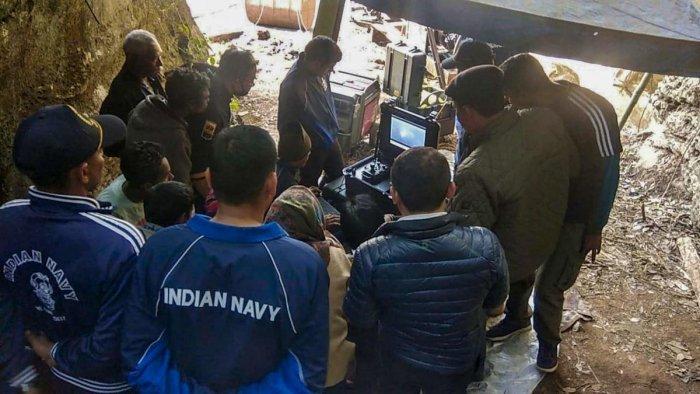 Naval divers look at the captured pictures of one of the 15 miners trapped in illegal rat mines since December 13, in Ksan area of East Jaintia Hills, on January 17, 2019. PTI