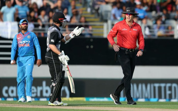 New Zealand's captain Kane Williamson (C) talks to an umpire about the wicket of Daryl Mitchell during the second Twenty20 international cricket match between New Zealand and India in Auckland on Friday. (AFP Photo)