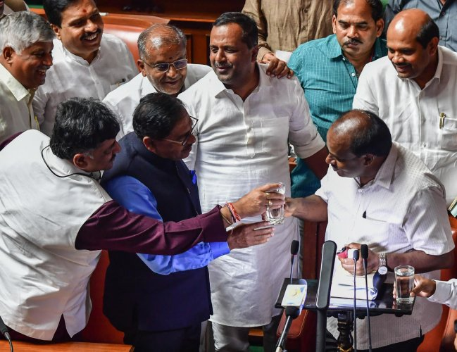 Minister D K Shivakumar and Deputy Chief Minister G Parameshwara offer a glass of water to Chief Minister H D Kumaraswamy after he completed his three-and-a-half-hour Budget speech in Bengaluru on Friday. DH Photo/Anand Bakshi