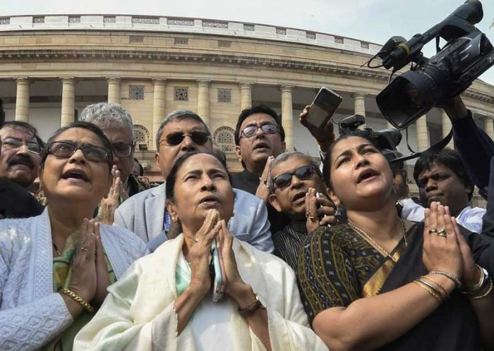 West Bengal Chief Minister and TMC supremo Mamata Banerjee with party MPs prays in front of the Mahatma Gandhi's statue inside Parliament complex in New Delhi on Wednesday. (PTI Photo)