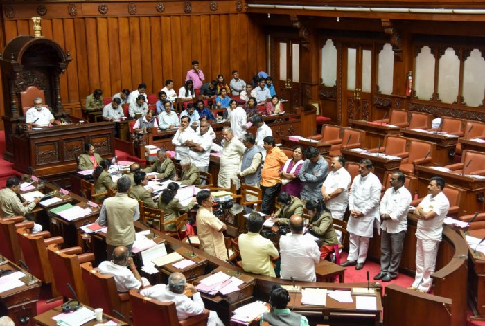 Din in Council: Opposition BJP members stage a protest against 'irregularities' in the execution of pure drinking water unit project in Legislative Council on Tuesday. DH photo