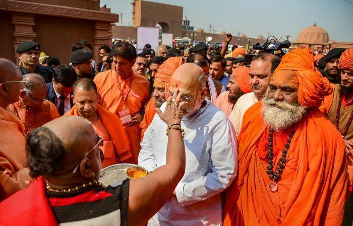 BJP president Amit Shah, accompanied by Uttar Pradesh Chief Minister Yogi Adityanath, meets the sadhus at Juna Akhara ashram during his visit to Kumbh Mela 2019 in Prayagraj (Allahabad), on Wednesday. PTI