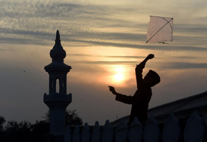 A Pakistani boy flies a kite on the roof of a mosque during sunset in Lahore on February 11, 2019. (Photo by ARIF ALI / AFP)