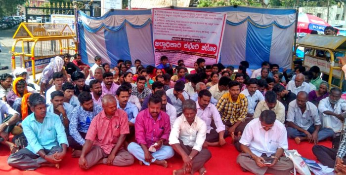 Members of Karnataka Adivasi Hakkugala Samanvaya Samithi, Belthangady taluk, in association with other organisations, stage a protest in front of deputy commissioner's office in Mangaluru on Friday.
