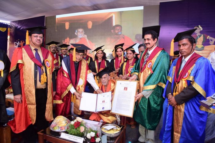 Srinivas University Chancellor A Raghavendra Rao confers an honorary doctorate on Pejawar seer Vishwesha Theertha Swami, during the first convocation of the university on Friday.