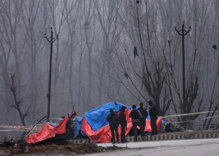 Forensic and security officials stand next to the wreckage of a bus after a suicide bomber rammed a car into the bus carrying Central Reserve Police Force (CRPF) personnel on Thursday, in Lethpora in south Kashmir's Pulwama district on Friday. (REUTERS)