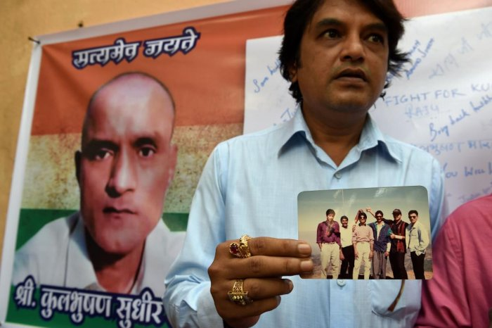 In this file photo taken on May 18, 2017 Indian friends of Kulbhushan Jadhav hold a photograph of them with Jadhav in the neighborhood where he grew up in Mumbai on May 18, 2017. - India will ask the UN's top court on February 18, 2019, to order Pakistan