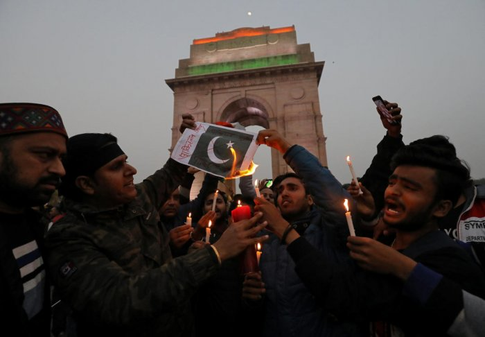People burn a poster depicting a Pakistani flag during a candle light vigil to pay tribute to Central Reserve Police Force (CRPF) personnel who were killed after a suicide bomber rammed a car into the bus carrying them in south Kashmir on Thursday, in fro
