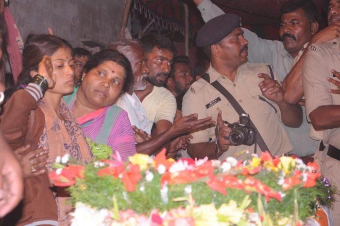 FINAL SALUTE: Kalavathy, wife of H Guru, at his coffin at Gudigere Colony in Maddur taluk, Mandya, on Saturday.