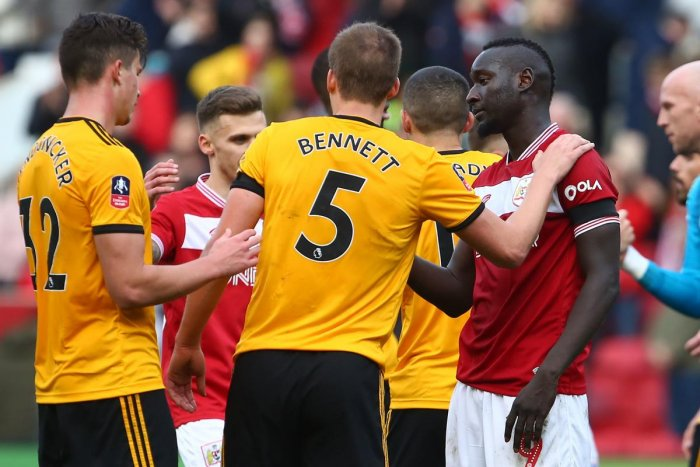 Wolverhampton Wanderers' English defender Ryan Bennett (C) consoles Bristol City's Senegalese striker Famara Diedhiou (R) on the pitch after the English FA Cup fifth round football match between Bristol City and Wolverhampton Wanderers at Ashton Gate Stad