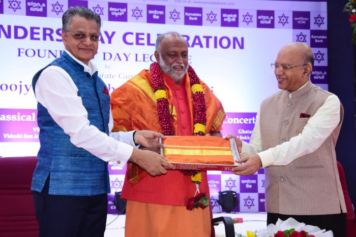 Corporate Guru Swami Sukhabodhananda, the main speaker at the Founders' Day celebration of Karnataka Bank, is felicitated by Bank Managing Director and CEO Mahabaleshwara M S and Chairman P Jayaram Bhat at the bank's head office in Mangaluru on Monday.