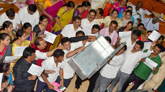 BJP councillors protest in the well of the council when S P Hemalatha, chairperson of the Standing Committee on Taxation and Finance, was presenting the budget on Monday. (DH Photo)