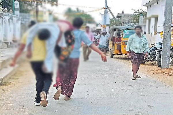 Villagers carrying Kotaiah from the check post where police have left him