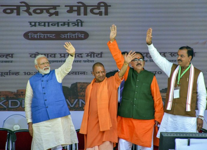 Prime Minister Narendra Modi, Uttar Pradesh Chief Minister Yogi Adityanath and his deputy Keshav Prasad Maurya wave as they inaugurate the different development program, in Varanasi, Tuesday, Feb 19, 2019. (PTI Photo)