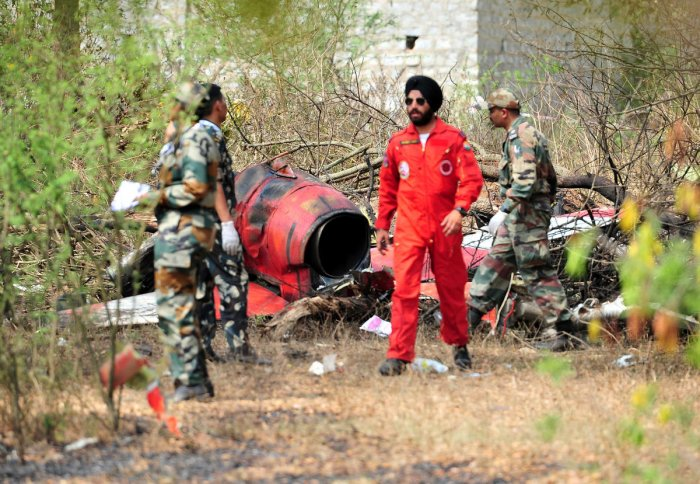 Soldiers stand near the wreckage after two Hawk aircraft of the Surya Kiran Aerobatic Display Team of the Indian Air Force collided in mid-air while rehearsing ahead of Aero India show at the Yelahanka Air Force Station in Bengaluru, India, February 19, 2