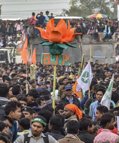 A BJP activist holds a model of party symbol 'lotus' as Prime Minister Narendra Modi addresses 'Save Democracy' rally at Churabhandar, Maynagiri in Jalpaiguri district of West Bengal, Friday, Feb 8, 2019.