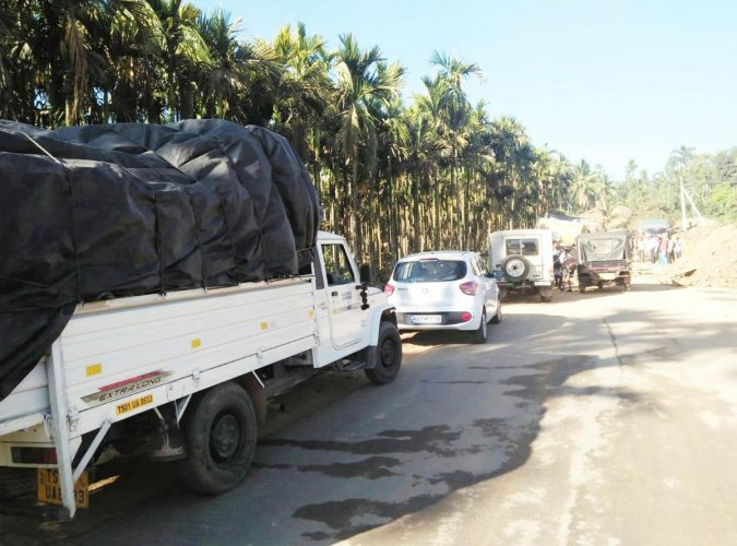 Vehicles lined up on National Highway 234 near Phalguni village in Mudigere on Thursday.