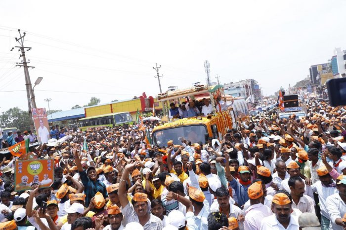 BJP chief Amit Shah waves to the crowd during the roadshow in Badami, Bagalkot district on Thursday. Party candidate B Sriramulu and chief ministerial candidate B S Yeddyurappa are also seen. dh photo