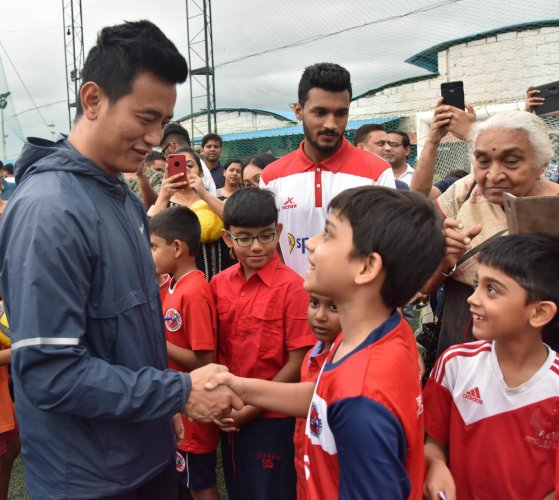 INSPIRATION Bhaichung Bhutia with aspiring young players during a promotional event on Sunday. DH PHOTO/ BK JANARDHAN