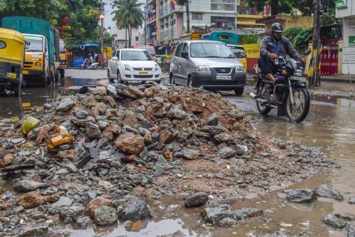 Building debris dropped on the road to fill potholes at Lakkasandra on Monday. DH Photo/S K Dinesh