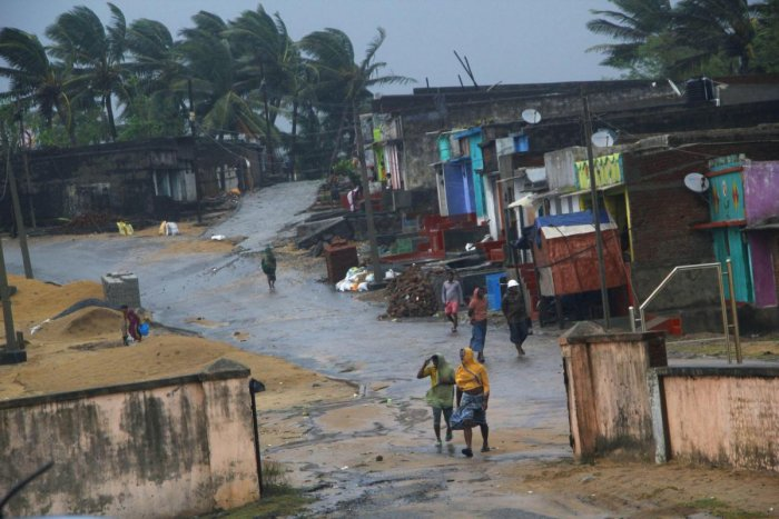 """Locals walk near their houses as Cyclone 'Titli' hits the coast, in Ganjam. The """"very severe"""" cyclonic storm left eight people dead, besides causing widespread damage in north coastal Andhra Pradesh Thursday, the State Disaster Management Authority (SDMA)"""