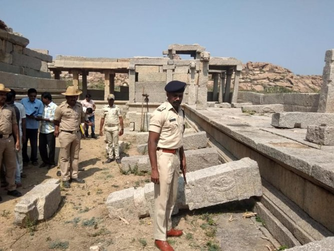 Police inspect the damage to the pillars in Hampi