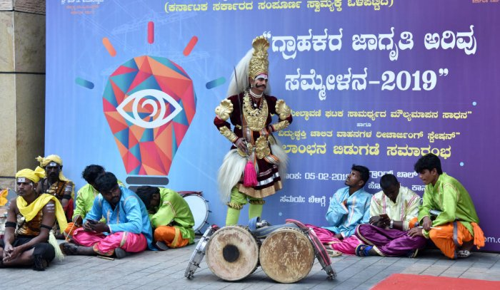 LONG WAIT: Folk artistes wait for Chief Minister H D Kumaraswamy for the inauguration of Customer Vigilance Awareness meet in Bengaluru on Tuesday. The programme was scheduled to start at 10.30 am and the chief minister arrived by 12.30 pm. DH Photo
