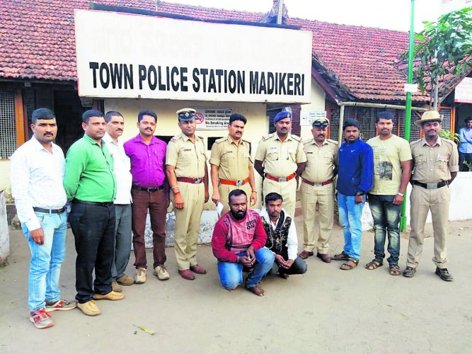 Madikeri Town police with the arrested, Mubarak and Syed Khalil, who had allegedly misused the name of District In-charge Minister Sa Ra Mahesh to cheat people, in Madikeri.