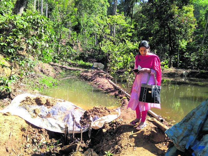 Kundacheri Gram Panchayat development officer inspects the spot where a planter has installed a mud wall against a stream and has diverted the water to his plantation in Kopatti village in Kodagu.
