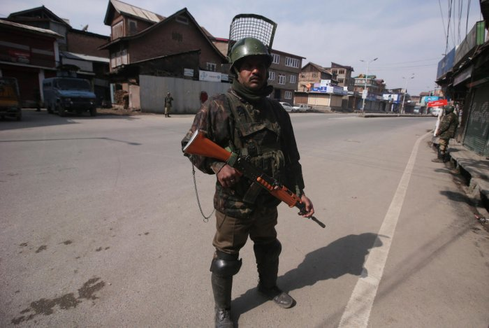 Indian Central Reserve Police Force (CRPF) personnel stand guard in front of closed shops during restrictions after Kashmiri separatist called for shutdown to protest the arrest of their leaders in Srinagar February 24, 2019. REUTERS/Danish Ismail