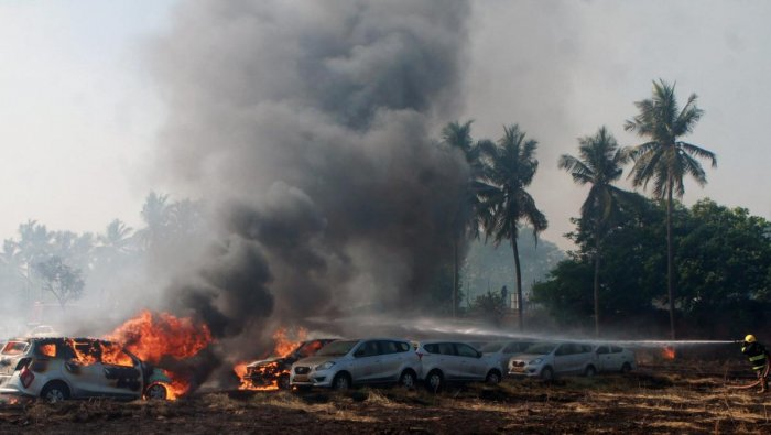 Smoke and flames rising after a major fire broke out in a car parking space opposite to Ramachandra Medical College in Porur, Chennai on Sunday. PTI photo