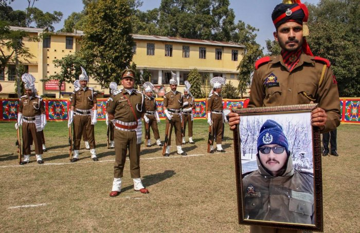 A police officer holds a portrait of Deputy Superintendent of Police Aman Kumar Thakur, who was killed in an encounter with militants in Kashmir's Kulgam district on Saturday, during a wreath laying ceremony in Jammu on Monday. PTI