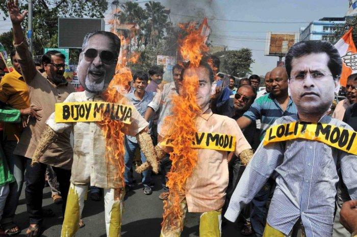 Congress activists burn effigies of Nirav Modi,Vijay Mallya and Lalit Modi during the demonstration protest, in Kolkata, Sunday, February 18, 2018. (PTI Photo)