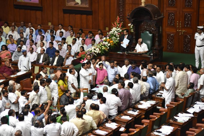 BJP legislators raise slogans in the Well of the House against constitution of an SIT to probe the audio tapes on 'Operation Lotus', in Vidhana Soudha, Bengaluru. DH Photo/ B H Shivakumar