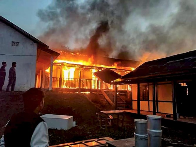 A building set on fire after a mob went on a rampage during a protest against the move to grant permanent resident certificates to six communities living in the state, in Itanagar on Sunday. PTI
