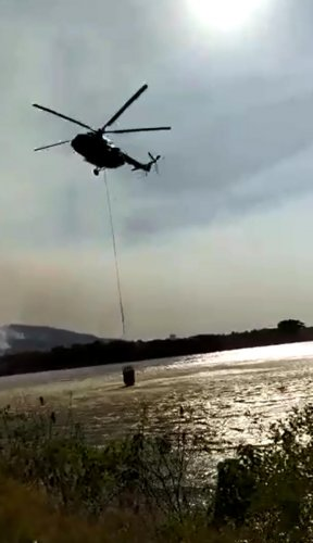 A video grab of a chopper lifting water from Berambadi lake near Bandipur forest area to douse the fire in the forest on Monday.
