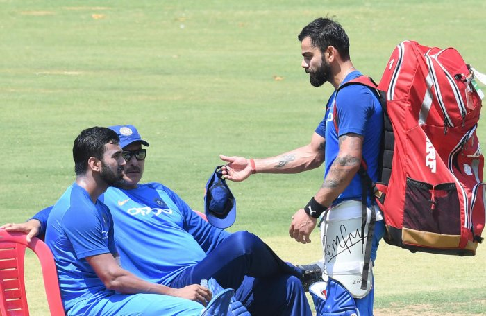 SERIOUS TALK: Indian captain Virat Kolhi (right) having a word with opener K L Rahul and head coach Ravi Shastri during their practice session at the M Chinnaswamy stadium in Bengaluru on Tuesday. DH Photo/ Srikanta Sharma R