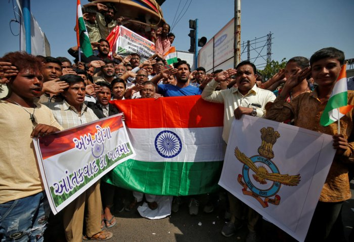 People hold national flags and an Indian Air Force flag as they salute to celebrate after Indian authorities said their jets conducted airstrikes on militant camps in Pakistani territory, in Ahmedabad, India, February 26, 2019. REUTERS