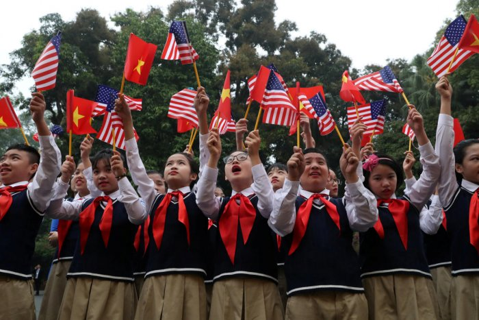 Students from Nguyen Du secondary school wave U.S. and Vietnam flags outside the Presidential Palace, as they wait to greet U.S. President Donald Trump, in Hanoi, Vietnam, February 27, 2019. REUTERS