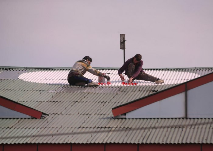 Workers paint a Red Cross sign on the rooftop of a hospital in Srinagar. (Reuters Photo)
