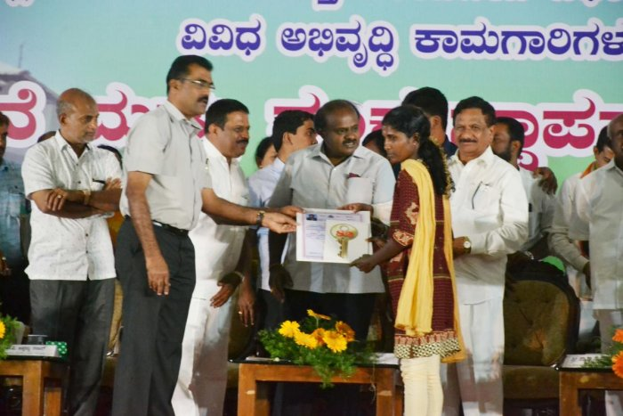 Chief Minister H D Kumaraswamy hands over the title deed of a house to one of the Diddalli evacuees at a programme in Kushalnagar on Thursday.