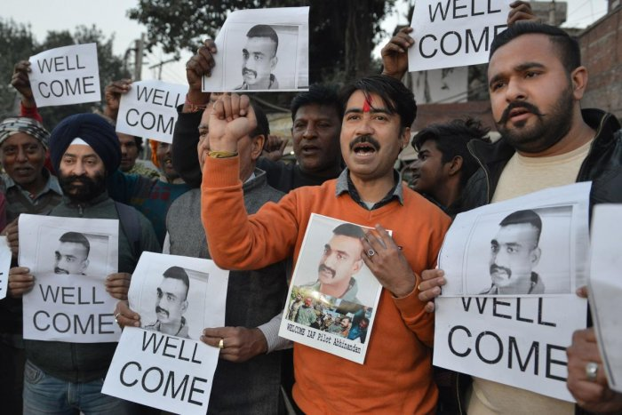 Indian people hold placards and photographs of Indian Air Force pilot Abhinandan Varthaman, as they celebrate the announcement of his soon release, in Amritsar on February 28, 2019. - Pakistan said on February 28 it will release a captured Indian pilot in