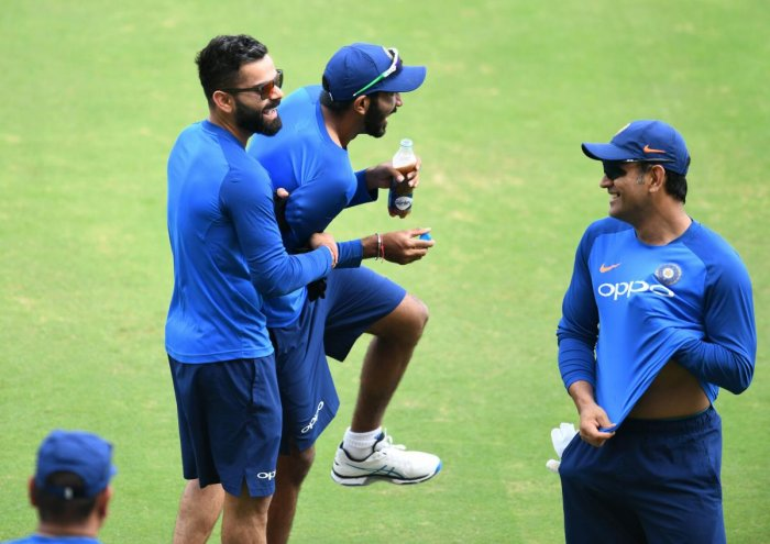 FUN AT WORK Indian captain Virat Kohli (left) in a playful mood with Jasprit Bumrah as MS Dhoni (R) looks on during a practice session in Hyderabad on Friday. AFP