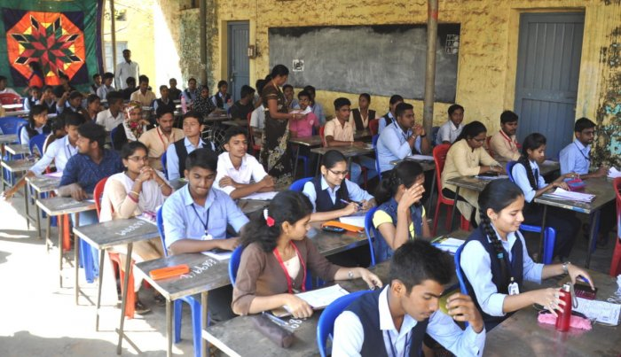 Students write II PU exams under scorching sun at the Govt Girls College in Hosapete on Thursday. The day temperatures in the town is hovering around 36 degrees Celsius. DH PHOTO