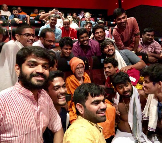 Pejawar Mutt seer watches Hindi film Uri with his followers in Manipal on Thursday night.