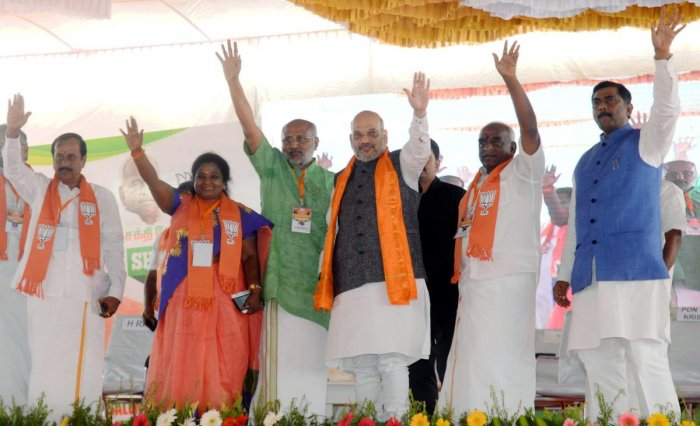 BJP National President Amit Shah waves at the gathering during a meeting of Handloom & Powerloom Associations in Erode, Tamil Nadu, Thursday, Feb 14, 2019. BJP Union Minister Pon Radhakrishnan (2nd R) is also seen. (Handout Photo via PTI)