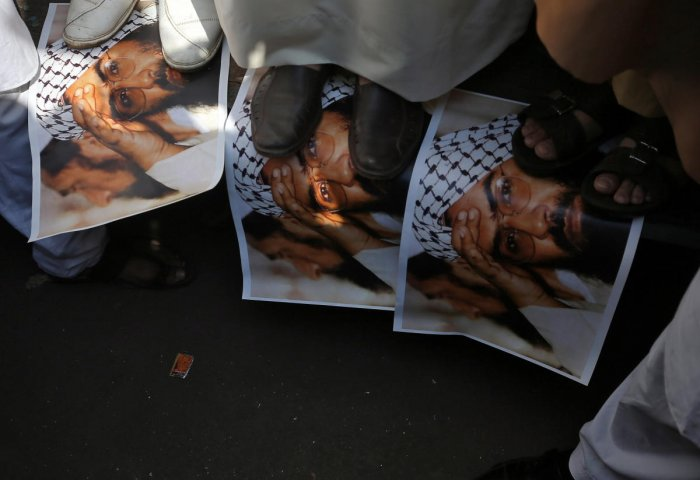 Demonstrators step on the posters of Maulana Masood Azhar, head of Pakistan-based militant group Jaish-e-Mohammad which claimed attack on a bus that killed 44 Central Reserve Police Force (CRPF) personnel in south Kashmir on Thursday, during a protest in